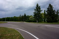 Een lege wegkruising en bomen die langs het in een sombere bewolkte dag groeien royalty-vrije stock afbeelding