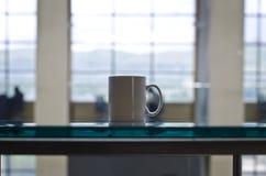 Een lege witte koffiemok op de lijst van het studieglas royalty-vrije stock afbeeldingen