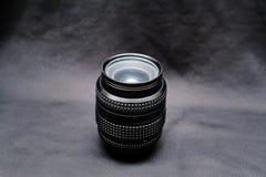 Een lens voor nikon op een zwarte achtergrond stock afbeelding