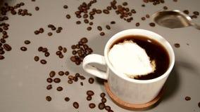 Een lepel room wordt toegevoegd aan vers gebrouwen koffie stock videobeelden
