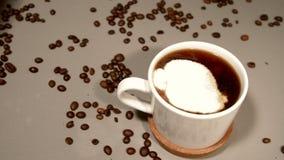Een lepel room wordt toegevoegd aan vers gebrouwen koffie stock video