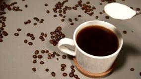 Een lepel suiker wordt toegevoegd aan vers gebrouwen koffie stock footage