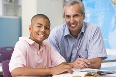 Een leraar instrueert een schooljongen Royalty-vrije Stock Afbeeldingen