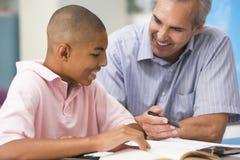 Een leraar instrueert een schooljongen Stock Foto's