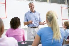 Een leraar spreekt aan schoolkinderen in een klasse Stock Foto