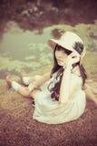 Een leuk Aziatisch Thais meisje ontspant dichtbij de vijver in wilderne Royalty-vrije Stock Foto's