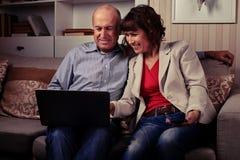 Een leuk bejaard paar die en een notitieboekje glimlachen bekijken Royalty-vrije Stock Foto's