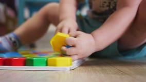 Een leuk kind verzamelt een beeld van grote multi-colored details Het spelen met een raadsel stock video