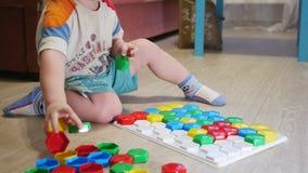 Een leuk kind verzamelt een beeld van grote multi-colored details Het spelen met een raadsel stock videobeelden