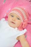 Een leuk klein babymeisje staart omhoog en is op een roze deken Stock Fotografie