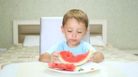 Een leuk klein kind zit bij de keukenlijst en eet een sappige watermeloen met een eetlust Bessen, vruchten stock video
