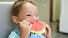 Een leuk klein kind zit bij de keukenlijst en eet een sappige watermeloen met een eetlust Gezichts lachende jongen stock videobeelden