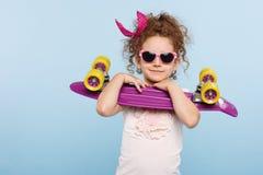 Een leuk klein krullend meisje, in zonnebril, die in studio met skateboard in handen houden, op een blauwe achtergrond worden ge stock afbeelding