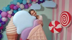 Een leuk meisje houdt een reusachtig roomijs in de studio op een achtergrond van reuzesnoepjes stock videobeelden