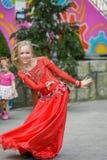 Een leuk meisje in een rood kostuum danst op de straat Meisje in de dansklasse Het babymeisje leert dans Toon dans aan stock foto