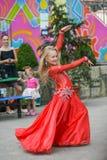 Een leuk meisje in een rood kostuum danst op de straat Meisje in de dansklasse Het babymeisje leert dans Toon dans aan royalty-vrije stock afbeeldingen