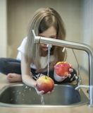 Een leuk meisje wast een rode gele appel in een gootsteen Het kind wast het fruit in keuken Weinig kind leert de regels stock foto's