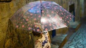 Een leuk meisje zit door de vulklei Dalingen van regenstroom onderaan een multi-colored paraplu De kindglimlachen en stock footage