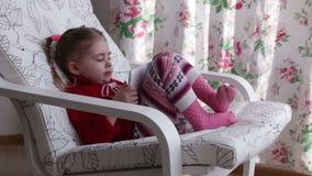 Een leuk meisje zit in leunstoel dichtbij venster het spelen met digitale tablet stock video