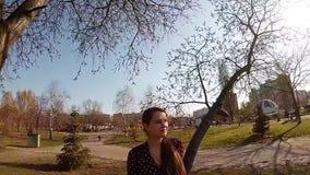 Een leuk zwanger meisje die haar buik strijken onder een boom stock video