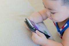 Een leuke Aziatische jongen gebruikt een smartphone stock fotografie