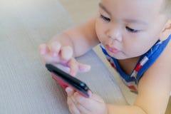 Een leuke Aziatische jongen gebruikt een smartphone stock foto's