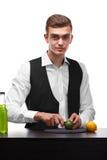 Een leuke barkeeper die groene die kalk snijden, op een witte achtergrond wordt geïsoleerd Fruitcocktail die concept maken De rui stock foto's