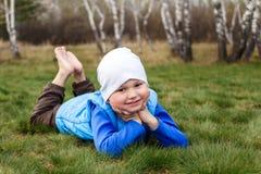 Een leuke glimlachende jongen in een blauw vest ligt op zijn maag, houdend zijn handen onder zijn kin op het groene gras royalty-vrije stock foto