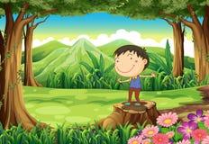 Een leuke jonge jongen boven de stomp bij de wildernis Royalty-vrije Stock Afbeeldingen