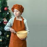 Een leuke jonge kok in oranje kleren houdt een kop voor het bewegen van voedsel terwijl het koken van deeg op de achtergrond van  Stock Foto