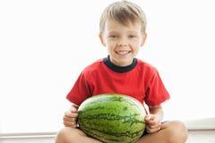 Een leuke jongen en een grote groene watermeloen royalty-vrije stock foto's
