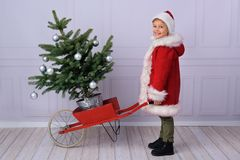 Een leuke jongen kleedde zich als Santa Claus, in een mooie rode schapehuidlaag, stock fotografie