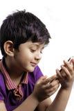 Een leuke jongen met mobiel Stock Afbeelding