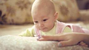 Een leuke kleine baby onderzoekt de camera stock video