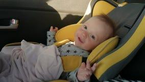 Een leuke kleine baby zit in een autozetel, een glimlach en een vreugde van reis stock video