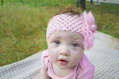Een leuke kleine baby zit op het gras buiten in het park Stock Foto's