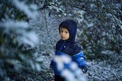 Een leuke kleine jongen bevindt zich in sneeuw in park in de winter, bekijkend de camera Royalty-vrije Stock Foto