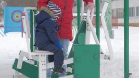 Een leuke kleine jongen en een jonge moeder zijn bezig geweest met openluchtoefeningsmateriaal Het ` s moeilijk voor een jong gei stock videobeelden