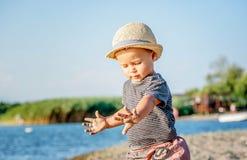 Een leuke kleine jongen met de zomerhoed het spelen in het zand op bea royalty-vrije stock afbeeldingen