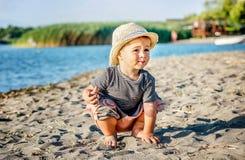 Een leuke kleine jongen met de zomerhoed het spelen in het zand op bea stock fotografie