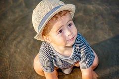 Een leuke kleine jongen met de zomerhoed het spelen in het zand op bea stock foto