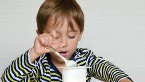 Een leuke kleine jongen van Europese verschijning zit bij de lijst en eet een zuivelproduct Het kind eet yoghurt Gezond stock videobeelden