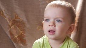 Een leuke kleine jongensjongen bekijkt aandachtig één punt Het glimlachen en verrast bij wat hij zag stock footage