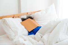Een leuke kleine slaap van het kind Afrikaanse Amerikaanse meisje en lui wanneer het lezen van het boek royalty-vrije stock fotografie