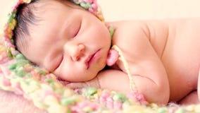 Een leuke slaapbaby in een gebreide hoed stock footage