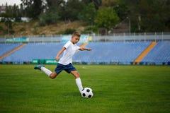 Een leuke tiener die de voetbalbal op een stadionachtergrond raken Kinderen die Voetbal opleiden Sportenconcept royalty-vrije stock afbeeldingen
