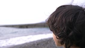 Een leuke tiener met krullend haar tegen de achtergrond van het overzees 4k, langzame motie stock videobeelden