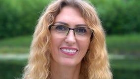 Een leuke vrouw op middelbare leeftijd met glazen en blond krullend haar voor de gek houdt rond, toont tong en glimlacht in aard  stock video