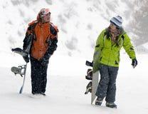 Een levensstijlbeeld van twee jonge volwassen snowboarders stock foto's
