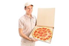 Een leveringsjongen die een pizza levert Stock Afbeeldingen